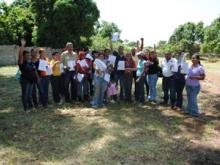 Retrato de las 12 personas beneficiarias con su título de propiedad de terreno.