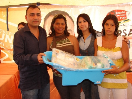 El alcalde Gustavo Muñiz y la Primera Dama del Municipio Piar entregando las canastillas a mujeres embarazadas.