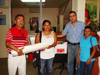 El alcalde Gustavo Muñiz entregando a la beneficiaria del Crédito lo necesario para reactivar su Librería.