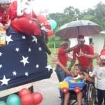 Los niños contentos reciben regalos de la mano de la Primera Dama